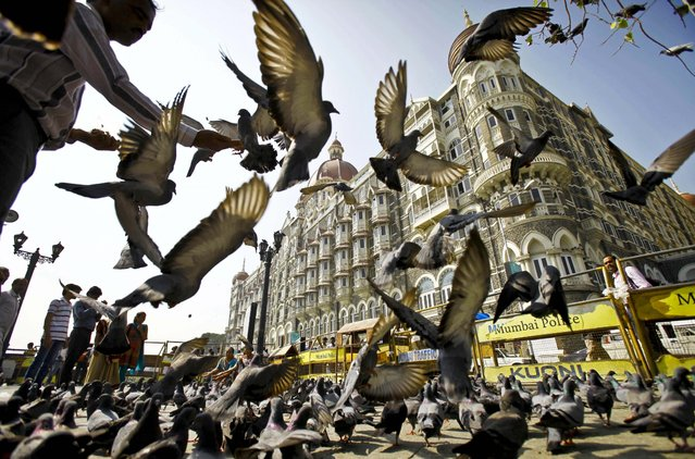 A man feeds pigeons outside the Taj Mahal hotel, one of the targets of the 2008 terror attacks in Mumbai, India, November 21, 2012. The lone surviving Pakistani gunman from the terror attack was executed earlier in the day providing much-needed closure over the three-day rampage that shook the nation's core and deepened enmity with neighbor Pakistan. (Photo by Rafiq Maqbool/Associated Press)