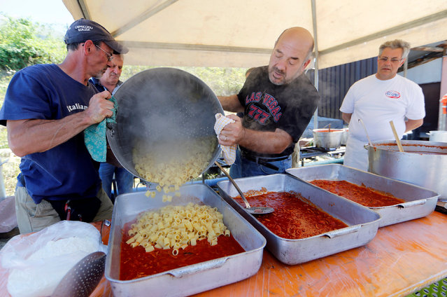 """Volunteers prepare """"Amatriciana"""", a type of pasta dish created in Amatrice, at a tent camp in Sant'Angelo, following an earthquake in central Italy, August 28, 2016. (Photo by Ciro De Luca/Reuters)"""
