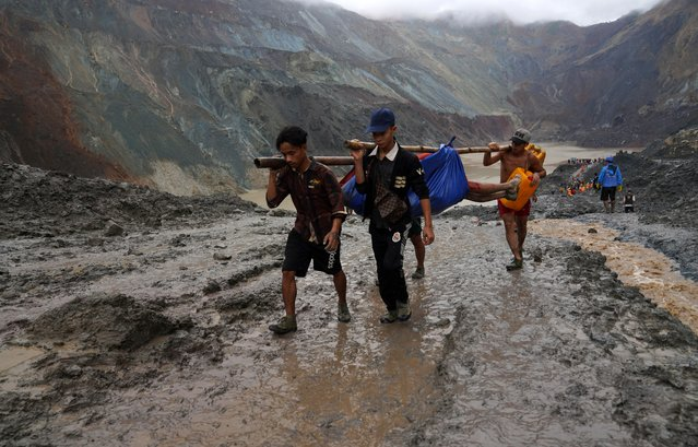 Rescuers recover a body near the landslide area in the jade mining site in Hpakhant in Kachin state on July 2, 2020. The battered bodies of more than 120 jade miners were pulled from a sea of mud after a landslide in northern Myanmar on July 2 after one of the worst-ever accidents to hit the treacherous industry. (Photo by Zaw Moe Htet/AFP Photo)