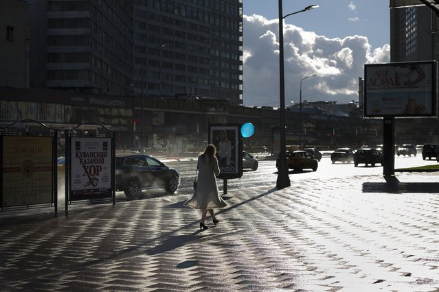 A young woman with a balloon walks through a sunny street right after a rain in Moscow, Russia, Thursday, September 8, 2016. Residents of the Russian capital are savoring the last days of warm weather before autumn's rain leads to a long dark Russian winter. (Photo by Alexander Zemlianichenko/AP Photo)