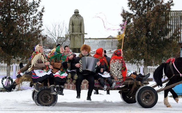 People sit on a horse-drawn cart as they attend Christmas celebrations in the town of Richev, some 290 km south from Minsk, on January 7, 2013. Orthodox Christians celebrate Christmas on January 7 in the Middle East, Russia and other Orthodox churches that use the old Julian calendar instead of the 17th-century Gregorian calendar adopted by Catholics, Protestants, Greek Orthodox and commonly used  attendsin secular life around the world. (Photo by Viktor Drachev/AFP Photo)