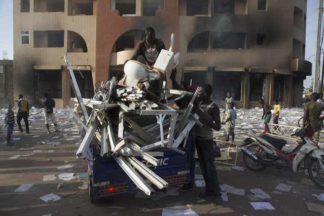 People load goods looted from a building, which according to locals, belongs to Francois Compaore, the younger brother of Burkina Faso's President Blaise Compaore, in Ouagadougou, capital of Burkina Faso, October 30, 2014. (Photo by Joe Penney/Reuters)