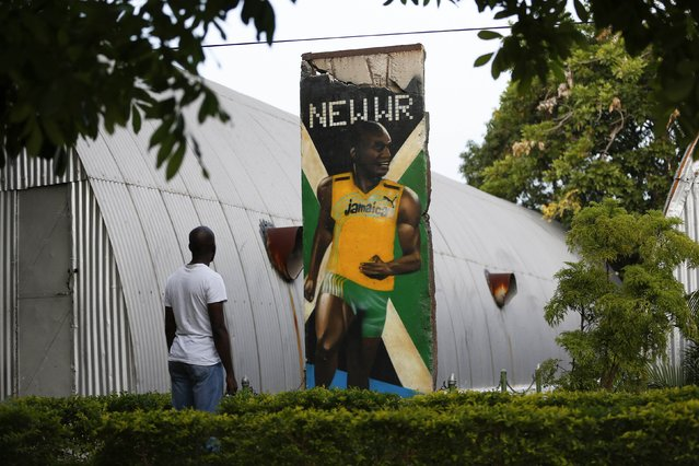 A visitor looks at a section of the Berlin Wall painted with a mural of Olympic champion Usain Bolt, at the Jamaica Military Museum and Library at Up Park Camp, headquarters of the Jamaica Defense Force in Kingston, September 13, 2014. The 12-foot section of the wall was given to Bolt in 2009 by the city of Berlin after the runner broke world records in the 100 and 200 meter finals of the World Athletics Championships in that city. (Photo by Gilbert Bellamy/Reuters)