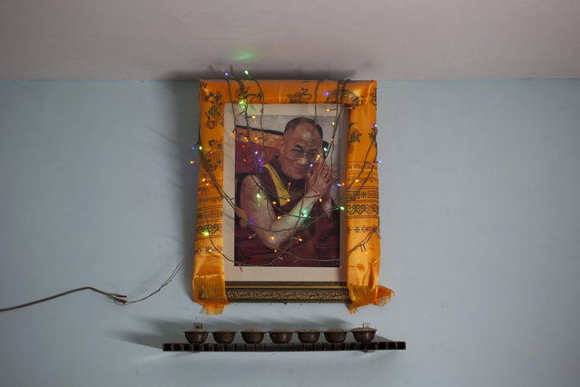 In this Tuesday, October 28, 2014 photo, a portrait of Tibetan spiritual leader the Dalai Lama hangs on a wall in a restaurant in New Delhi, India. Since the Dalai Lama fled a failed 1959 uprising against Chinese rule, tens and thousands of Tibetans have taken refuge in India, taking a weekslong walk to cross over the Himalayas from Tibet to India. (Photo by Tsering Topgyal/AP Photo)