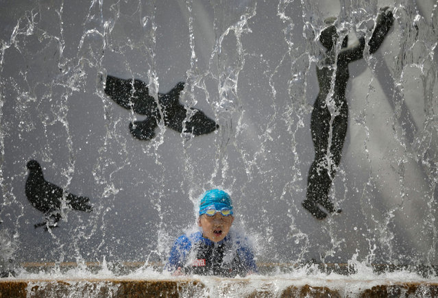 A child cools off under a public fountain, amid the coronavirus disease (COVID-19) outbreak, during hot summer weather at a park in Tokyo, Japan on August 13, 2020. (Photo by Issei Kato/Reuters)