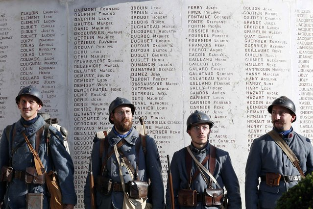 """History enthusiasts of French association """"Le Poilu de la Marne"""" stand in front of the war memorial during an Armistice Day ceremony to commemorate the end of World War One at Epernay, eastern France, November 11, 2014. (Photo by Charles Platiau/Reuters)"""