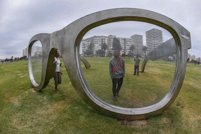"""People look at a stainless steel sculpture of a pair of spectacles titled """"Perceiving Freedom"""", a sculptural tribute to former South African president Nelson Mandela on the Sea Point promenade in Cape Town, South Africa, November 11, 2014. (Photo by Nic Bothma/EPA)"""
