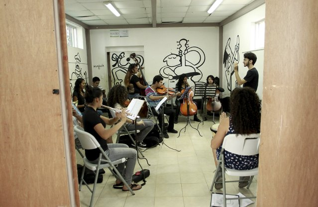 An orchestra comprised of youths of the poor neighborhood of La Carpio practice at the Integral System of Artistic Education for Social Inclusion (SIFAIS) center in La Carpio, August 29, 2015. (Photo by Juan Carlos Ulate/Reuters)