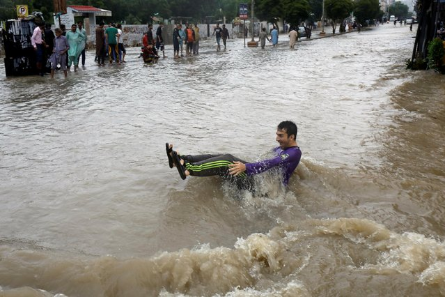 A man looses his balance while crossing a flooded street during monsoon rain, as the outbreak of the coronavirus disease (COVID-19) continues, in Karachi, Pakistan on August 27, 2020. (Photo by Akhtar Soomro/Reuters)