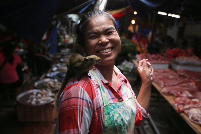 A woman walks with a squirrel on her shoulder at Maeklong market at the outskirts of Bangkok, Thailand September 20, 2016. (Photo by Jorge Silva/Reuters)