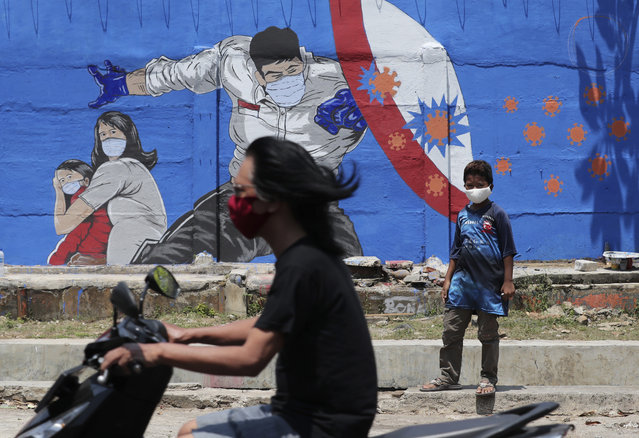 A young boy stands near a coronavirus-themed mural as a motorist rides past by in Jakarta, Indonesia, Thursday, August 27, 2020. (Photo by Tatan Syuflana/AP Photo)