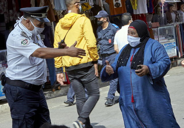 A Moroccan police officer reminds buyers to respect the security measures such as distancing and wearing a mask in a market of Casablanca, Morocco, Monday, September 21, 2020. Morocco first decreed lockdown measures on March 20. Today, police checks are part of the scenery in hard-hit Casablanca, the country's economic powerhouse, or Marrakech, a major tourist destination at a standstill. (Photo by Abdeljalil Bounhar/AP Photo)