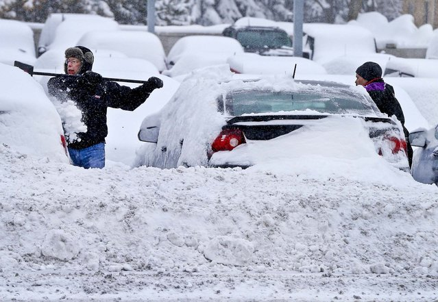 Workers remove snow from cars at an auto dealership in Bloomington, Minnesota, from a storm that is crawling east from the Dakotas and Minnesota toward Chicago which could bring up to 10 inches of snow in some areas, on March 5, 2013. (Photo by Jim Mone/Associated Press)