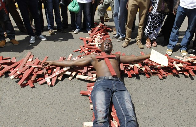 A protester lies on top of wooden crosses, symbolising people killed in a series of attacks, during the #OccupyHarambeeAve protest in Kenya's capital Nairobi November 25, 2014. (Photo by Thomas Mukoya/Reuters)