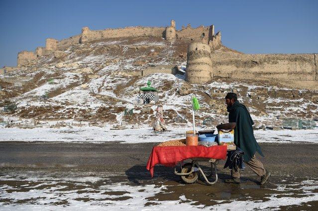 An Afghan vendor pushes a wheelbarrow after the first snowfall near the old fortress of Bala Hissar in Kabul on December 15, 2017. (Photo by Wakil Kohsar/AFP Photo)