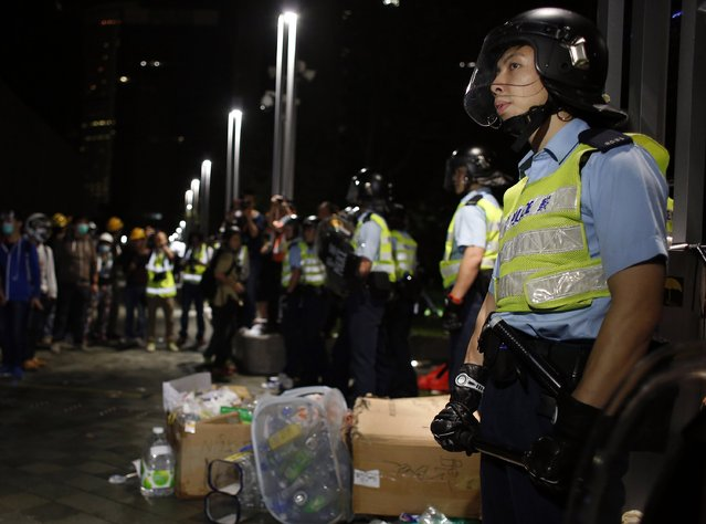 Riot policemen stand guard in front of pro-democracy protesters during a confrontation outside government headquarters in Hong Kong early December 1, 2014. (Photo by Bobby Yip/Reuters)