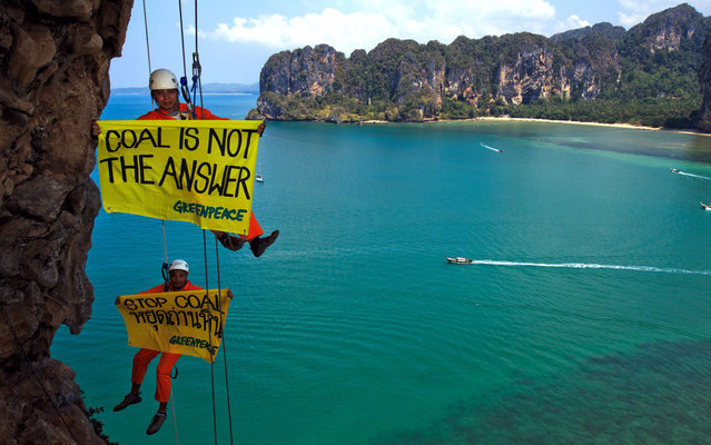 In this handout picture released by Greenpeace, activists displaying banners against coal plants hang from a cliff at Railay Beach in Krabi, some 700 kilometres south of Bangkok on March 21, 2013. The Thai government plans to build several coal plants across the country, one of them in Krabi province, in projects opposed by local communities and Greenpeace. (Photo by Athit Perawongmetha/AFP Photo/Greenpeace)