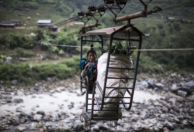 A local Nepalese woman crosses the Trishuli River using a rope bridge, known locally as a Tuin, near the village of Fhading Village in Dhading Disrict, some 90 kilometers from capital Kathmandu, Nepal, December 4, 2014. Farmers, students and villagers from the other side of the Trishuli river have to use different methods to cross after local authorities failed to build a promised bridge. (Photo by Narendra Shrestha/EPA)