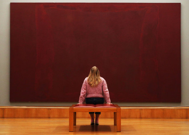 """A Tate employee sits before one of Mark Rothko's Seagram Murals entitiled """"Maroon on Maroon"""" during a photocall for the new collection displays at Tate Britain in London on October 15, 2020. (Photo by Jonathan Brady/PA Images via Getty Images)"""