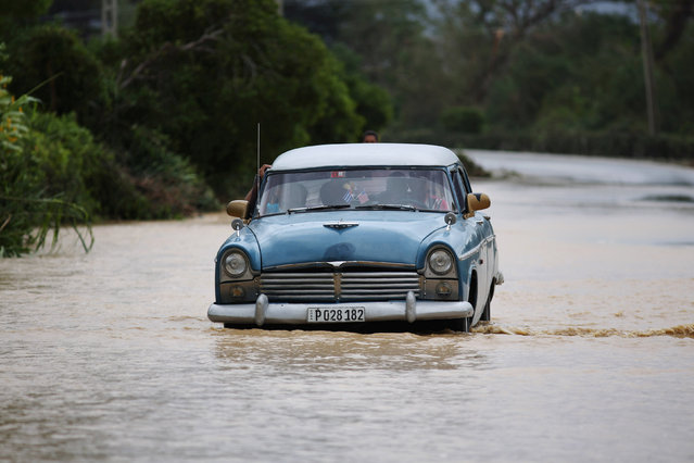 A vintage car crosses a flooded highway after the passage of Hurricane Matthew at Guantanamo Province in Cuba, October 6, 2016. (Photo by Alexandre Meneghini/Reuters)