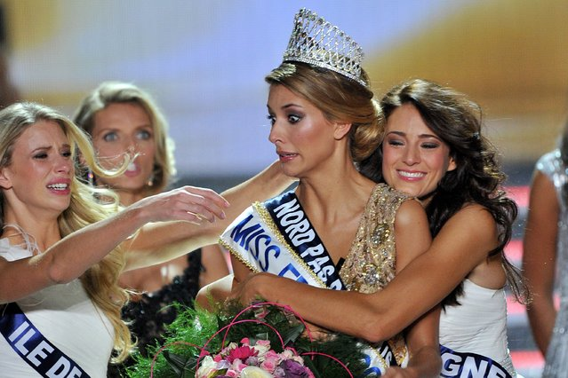 Miss Nord-Pas-de-Calais Camille Cerf (C) is congratulated by Miss Ile de France 2014 Margaux Savary (L) and Miss Auvergne 2014 Morgane Laporte after Cerf won the Miss France 2015 beauty contest on December 6, 2014 in Orleans. (Photo by Guillaume Souvant/AFP Photo)