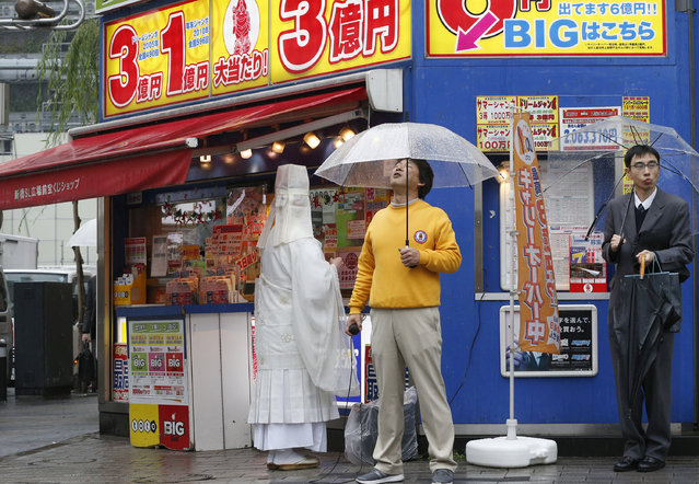 A monk chants a Buddhist mantra in front of a public lottery counter in Tokyo, Tuesday, November 25, 2014. Lottery stand owners hire monks to conduct ritual purification on their stands for a big win. (Photo by Shizuo Kambayashi/AP Photo)