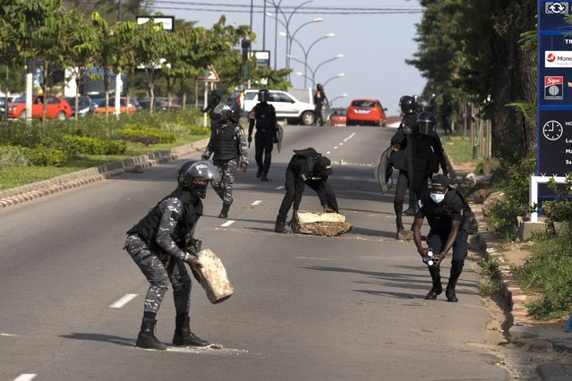 Riot police remove a barricade set up by demonstrators as they block access to the house of the former president Henri Konan Bedie, in Abidjan, Ivory Coast, Tuesday, November 3, 2020. Ivory Coast's electoral commission said Tuesday that President Alassane Ouattara had overwhelmingly won a third term in office after his two main opponents boycotted the election and called his candidacy illegal. (Photo by Leo Correa/AP Photo)