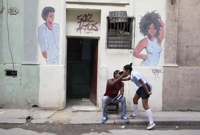 A man greets a friend outside a beauty salon in Havana December 17, 2014. (Photo by Reuters/Stringer)