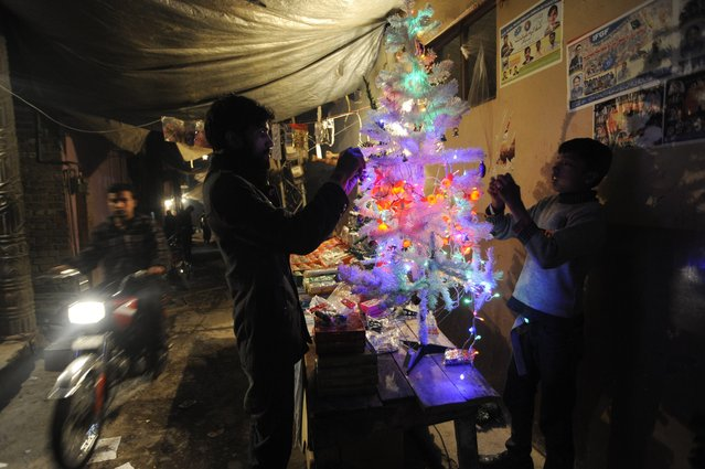 Pakistani Christians decorate a Christmas tree on a street in Islamabad, Pakistan, 24 December 2014. Christians in Pakistan form the country's largest minority, accounting for 1,6 per cent of the population. (Photo by T. Mughal/EPA)