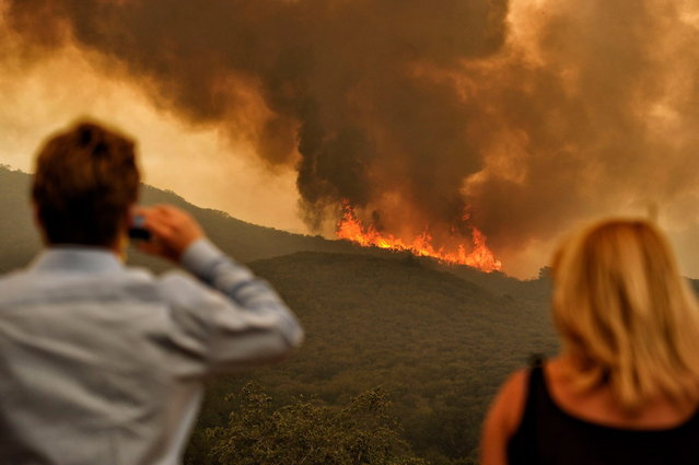 Residents watch the flames of wildfire move closer to their homes along W Potrero Rd., Friday, May 3, 2013 in Thousand Oaks, Calif. A huge Southern California wildfire burned through coastal wilderness to the beach on Friday then stormed back through canyons toward inland neighborhoods when winds reversed direction. (Photo by Hans Gutknecht/AP Photo/Los Angeles Daily News)