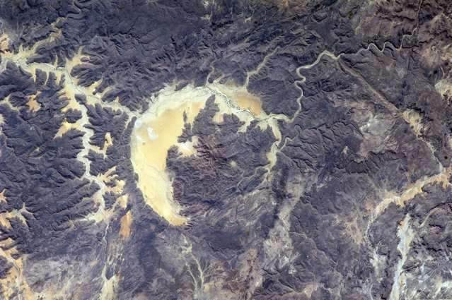 A photograph of The Gweni-Fada impact crater taken by astronauts on board the International Space Station on April 01, 2014 in Chad. Gweni-Fada measures 14 kilometres in diameter and formed around 360 million years ago on April 1, 2014 at Gweni-Fada, Chad. (Photo by NASA/SPL/Barcroft Media)