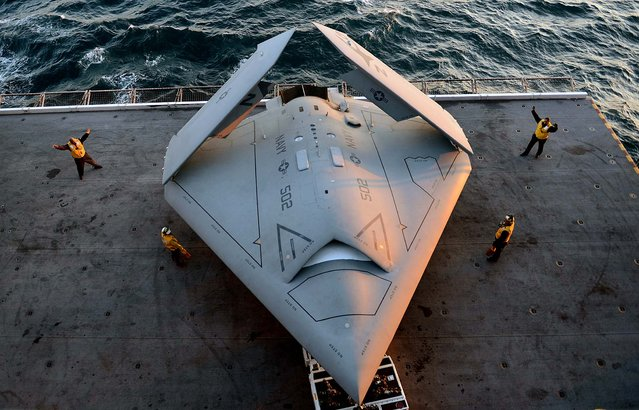 In this handout released by the U.S. Navy, Sailors move an X-47B Unmanned Combat Air System (UCAS) demonstrator onto an aircraft elevator aboard the aircraft carrier USS George H.W. Bush (CVN 77) May 14, 2013 in the Atlantic Ocean. George H.W. Bush is scheduled to be the first aircraft carrier to catapult-launch an unmanned aircraft from its flight deck. The Navy plans to have unmanned aircraft on each of its carriers to be used for surveillance and be armed and used in combat roles. (Photo by Mass Communication Specialist 2nd Class Timothy Walter/U.S. Navy via Getty Images)