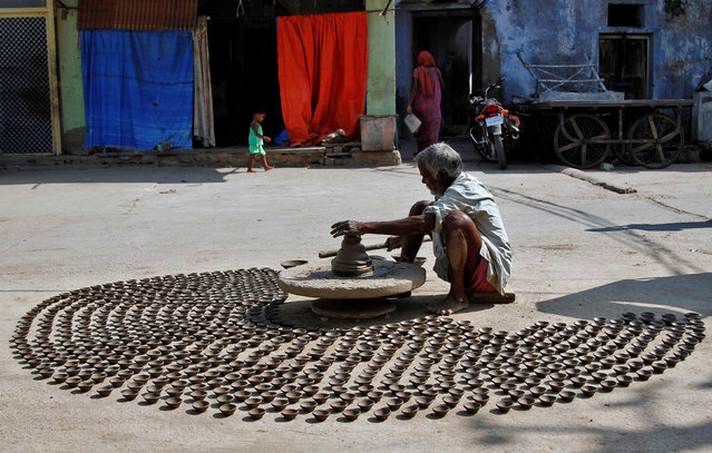 A man makes earthen lamps which are used to decorate temples and homes during the Hindu festival of Diwali, on a street in Ajmer, India October 17, 2016. (Photo by Himanshu Sharma/Reuters)