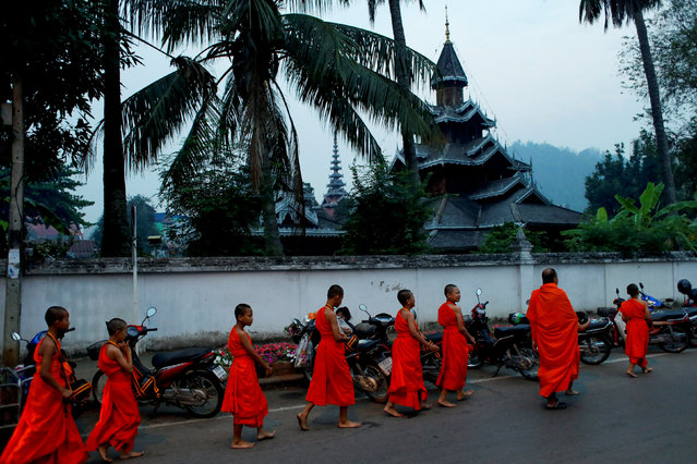Boys walks for almsgiving early morning after entering the Buddhist novicehood at a temple where they live for one or two months during their school holidays, studying Buddhist scripture, in Mae Hong Son, Thailand, April 15, 2018. (Photo by Jorge Silva/Reuters)