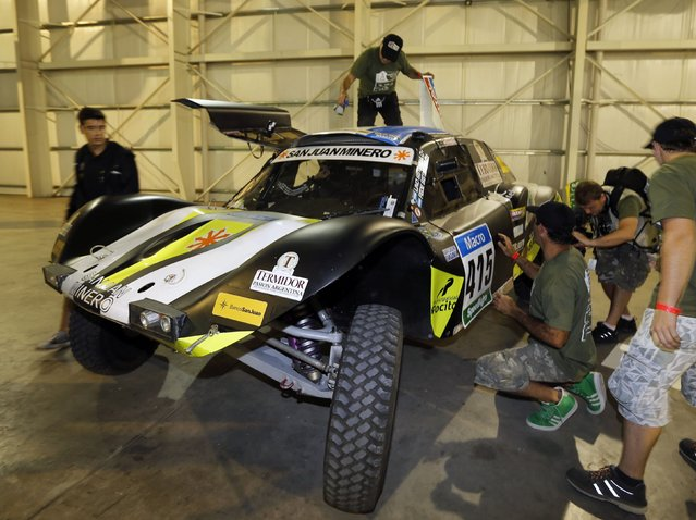 Mechanics work in the Buggy belonging to Argentina's Manuel Sisterna and Adrian Echegaray during technical verification ahead of the Dakar Rally 2015 in Buenos Aires January 1, 2015. (Photo by Enrique Marcarian/Reuters)