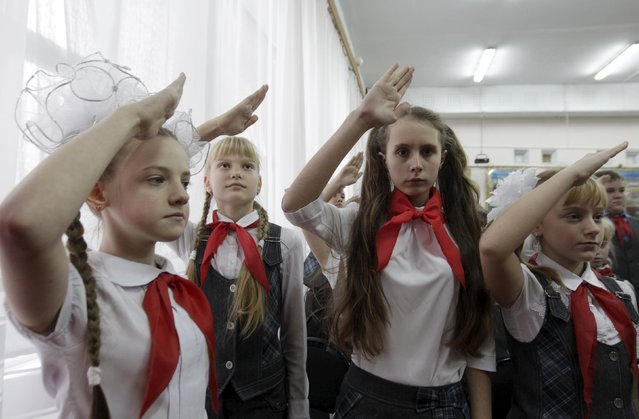 Children, wearing red neckerchiefs, a symbol of the Pioneer Organization, salute during a ceremony for the inauguration of 18 new members at a local school in the southern settlement of Kazminskoye in Stavropol region, Russia, November 19, 2015. Early pro-communist youth movements, which appeared in Russia after the 1917 Bolshevik revolution, were reformed into the Pioneer Organization of the Soviet Union. (Photo by Eduard Korniyenko/Reuters)