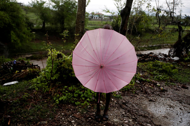 A boy looks above as he hides himself behind an umbrella after Hurricane Matthew in Les Cayes, Haiti, October 21, 2016. (Photo by Andres Martinez Casares/Reuters)