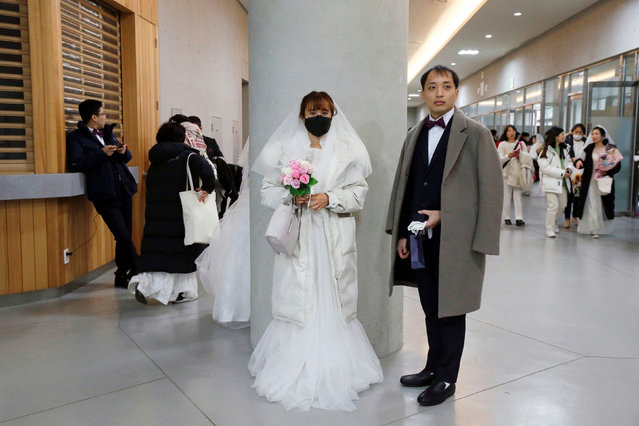A bride wearing a mask for protection from the new coronavirus, attends a mass wedding ceremony of the Unification Church at Cheongshim Peace World Centre in Gapyeong, South Korea, February 7, 2020. South Korea has confirmed 24 cases of the SARS-like virus so far and placed nearly 260 people in quarantine for detailed checks amid growing public alarm. (Photo by Heo Ran/Reuters)