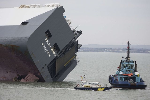 The cargo ship Hoegh Osaka lies on its side after being deliberately ran aground on the Bramble Bank in the Solent estuary, near Southampton in southern England January 5, 2015. (Photo by Peter Nicholls/Reuters)