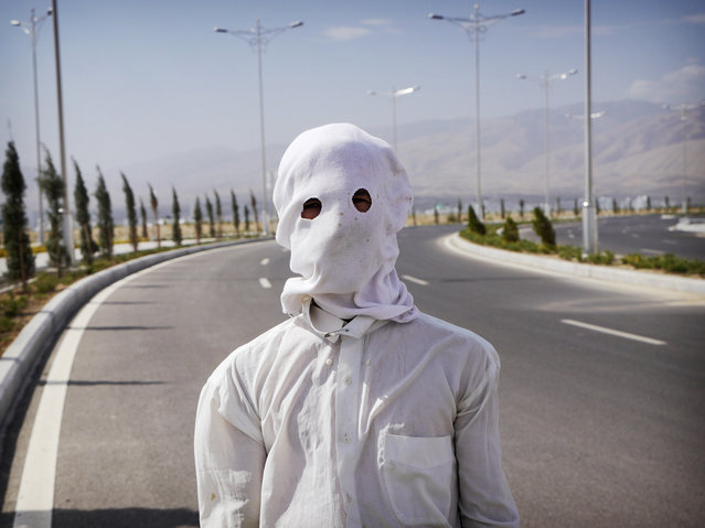 A gardener shrouded against the sun on a 104F (40C) day in Ashgabat. Despite their country's wealth, ordinary people receive little economic trickle-down. Workers like this one earn around $150 a month maintaining the white marble city. (Photo by Amos Chapple via The Atlantic)
