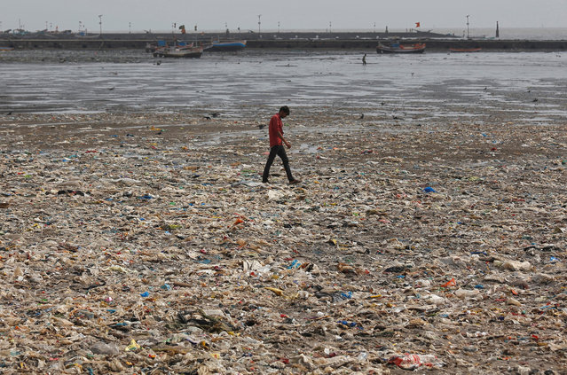 A man walks on a garbage-strewn beach in Mumbai, India, May 28, 2018. (Photo by Francis Mascarenhas/Reuters)