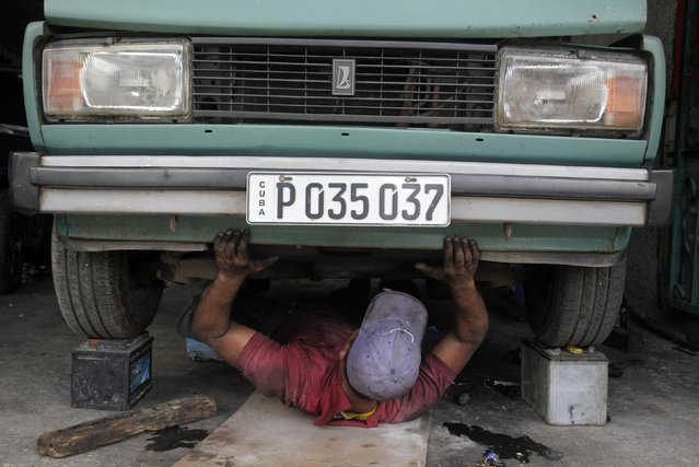 A mechanic works on a car at a shop in Havana January 15, 2015. The United States rolled out a sweeping set of measures on Thursday to significantly ease sanctions on Cuba, opening up the country to expanded U.S. travel, trade and financial activities. The 54-year-old U.S. embargo on Cuba will remain in place - only Congress can lift it. (Photo by Reuters/Stringer)