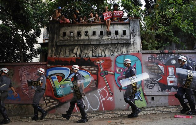 """People sitting on top of a wall hold signs that read, """"No to fare hikes"""", as riot police walk past below, during a protest against fare hikes for city buses, subways and trains in Sao Paulo January 16, 2015. (Photo by Nacho Doce/Reuters)"""