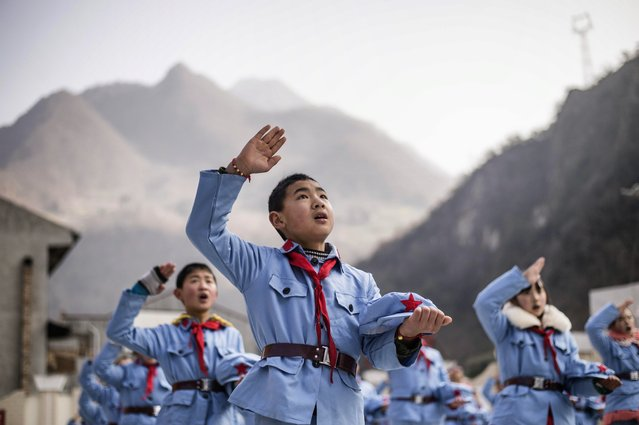 Children dressed in uniform sing after raising the national flag at the Beichuan Red army elementary school in Beichuan, southwest China's Sichuan province, on January 21, 2015. (Photo by Fred Dufour/AFP Photo)