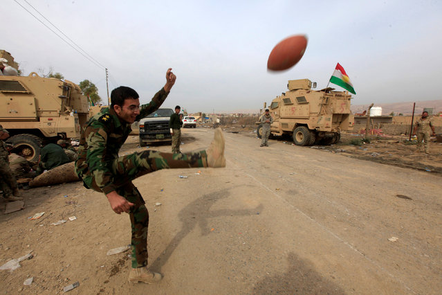 A member of Peshmerga forces play with a football in the town of Bashiqa, after it was recaptured from the Islamic State, east of Mosul, Iraq November 10, 2016. (Photo by Alaa Al-Marjani/Reuters)