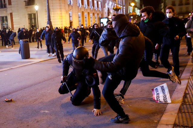 Demonstrators kick a police officers as supporters of Catalan rapper Pablo Hasel protest against his arrest in Madrid, Spain, February 17, 2021. (Photo by Susana Vera/Reuters)