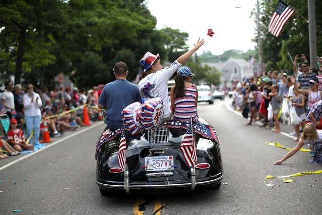 A boy throws candies from a vintage car as he rides on Main Street in the annual Fourth of July parade in Barnstable Village on Cape Cod, Massachusetts, U.S., July 4, 2018. (Photo by Mike Segar/Reuters)