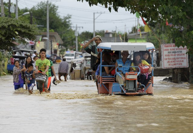 Residents wade through a flooded street after heavy rain at Candaba town, Pampanga province, north of Manila, December 17, 2015. Nine people were killed and hundreds spent the night huddled on their roofs in the central Philippines as floods generated by a powerful typhoon inundated villages, disaster officials said on Wednesday. (Photo by Czar Dancel/Reuters)