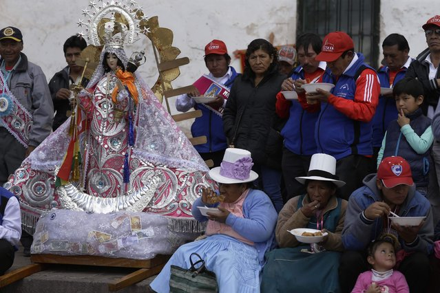 """In this Sunday, August 5, 2018 photo, """"cargadores"""" or male carriers and devotees lunch on free bowls of beef and wheat soup during a pause in the religious procession honoring Our Lady of Copacabana, in Cuzco, Peru. It is expected that the organizers provide free food and drink along with a small fee for the dancers and musicians. According to the steward of this year's celebrations, expenditures totaled 9,000 U.S. dollars. (Photo by Martin Mejia/AP Photo)"""