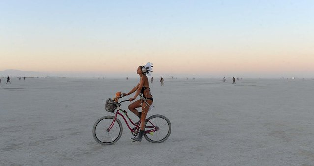 A woman rides a bicycle on the playa after sunset at the Burning Man festival in Gerlach, Nev. on Friday, Aug. 30, 2013. Once a year, tens of thousands of participants gather in Nevada's Black Rock Desert for the counterculture event. (Photo by Andy Barron/AP Photo/Reno Gazette-Journal)